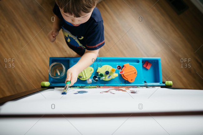 A boy paints on an easel