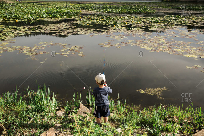 A small boy fishes at a lake shore