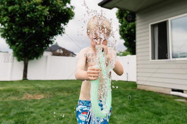 A boy blows water through a pool toy