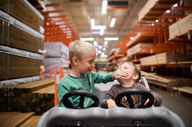Boys play in a toy shopping cart at a home improvement store