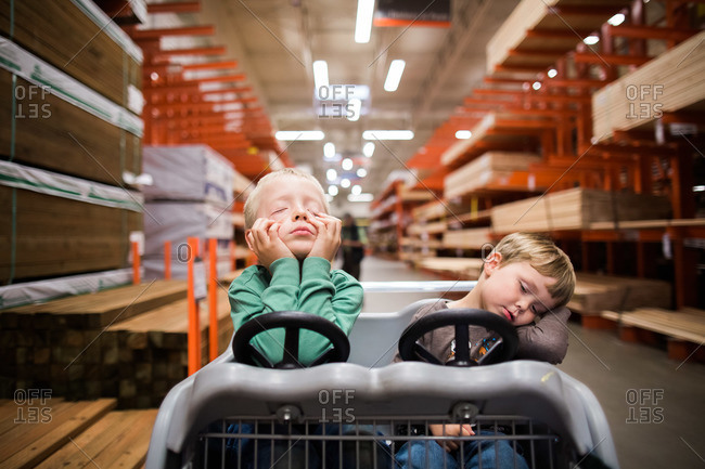Boys nap in a toy shopping cart at a home improvement store