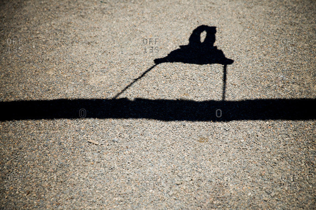 The shadow of a swinging child cast on gravel