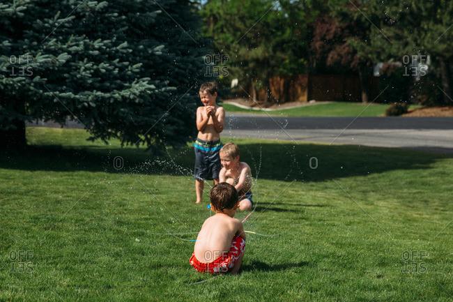 Three boys play in a toy lawn sprinkler