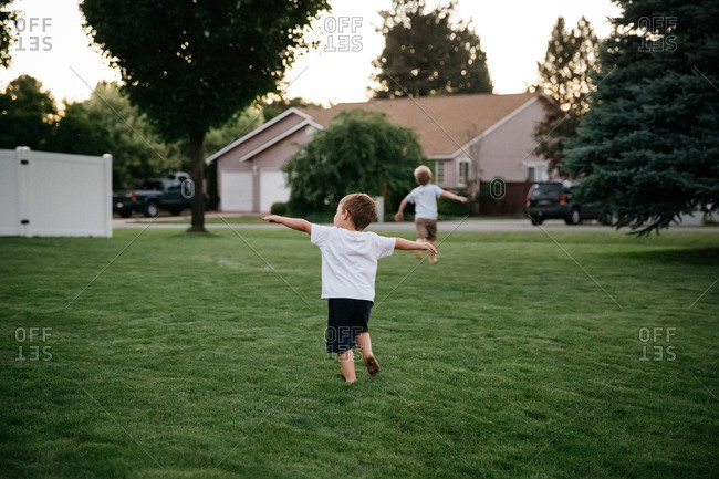 Two boys run barefoot on a lawn