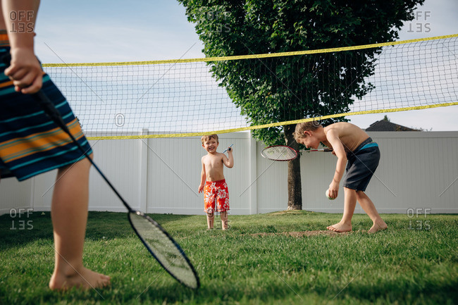 Boys play badminton on the lawn