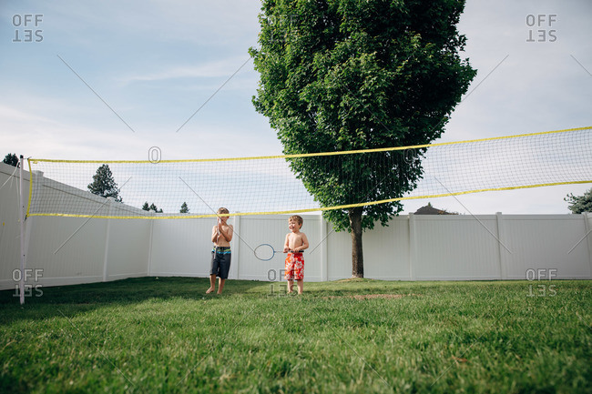 Two boys play badminton on the lawn