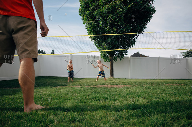 Two boys play badminton with their father