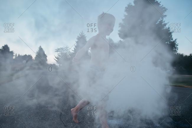 A boy walks in the smoke of a novelty firework