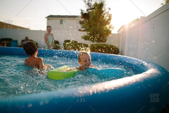 Boys splash in a inflatable pool