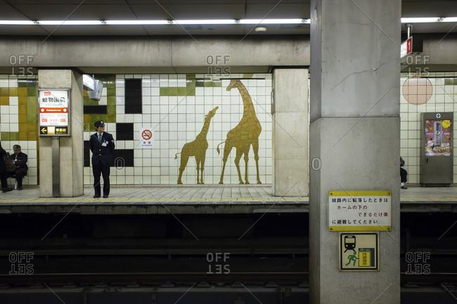 Japan - November 30, 2013: Station guard standing in Japanese train station