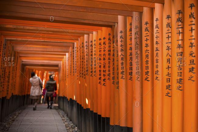 Japan - January 17, 2015: Couple walking through wooden tunnel, Japan