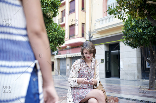 Young woman sitting on bench checking her smartphone