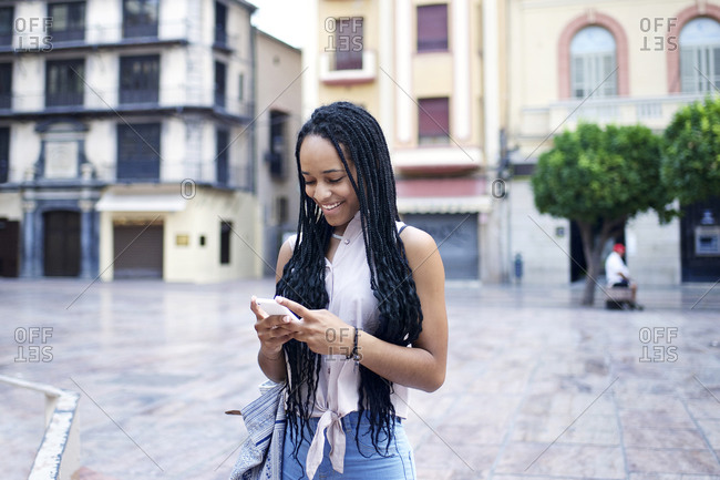 Woman with long braids checking smartphone in European square