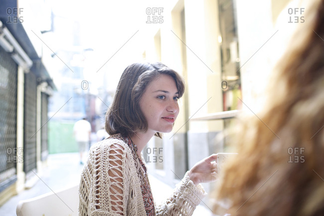 Young woman drinking coffee in an outdoor caf_