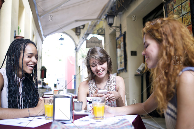 Three young women relax together at outdoor cafe