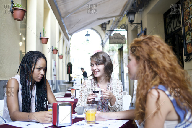 Three friends sit together at an outdoor caf_