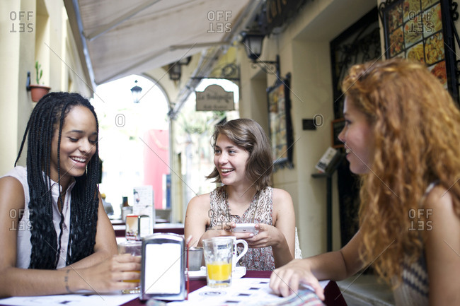Three friends talk while seated at an outdoor caf_