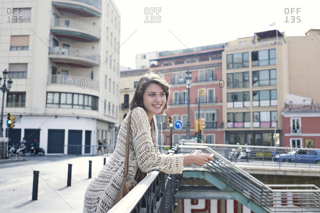 Sightseeing young woman with smartphone on bridge in European city