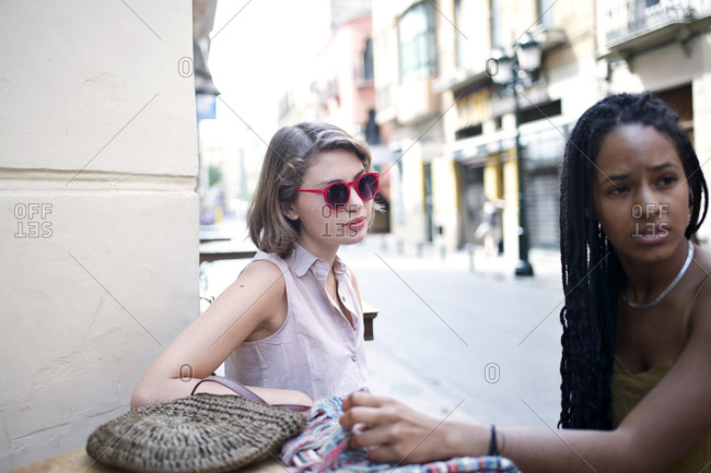 Two young women sitting at a caf_ on European street
