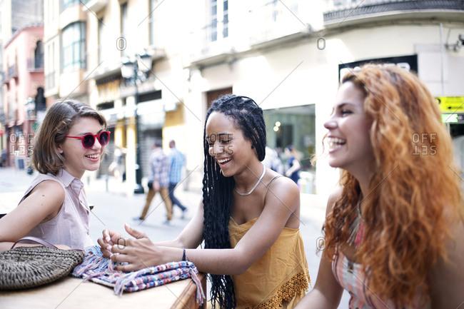 Three friends talk and laugh at a European street caf_