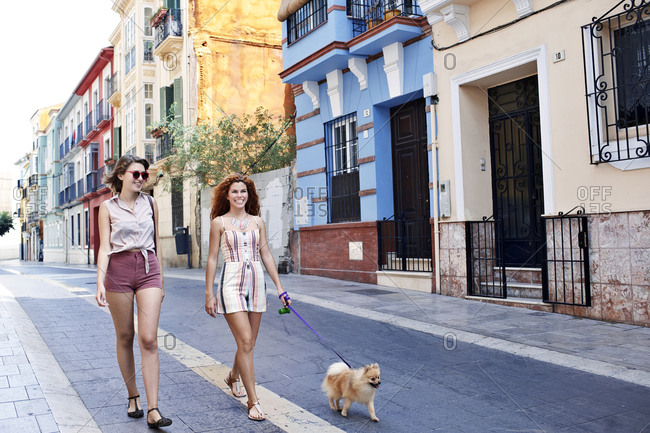 Woman walks her dog with a friend on a European street