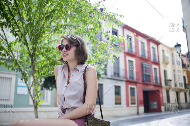 Young woman in sunglasses sitting near a tree on a picturesque European street
