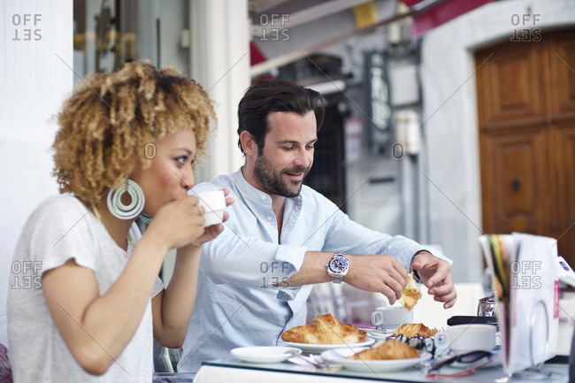 Man and woman enjoy coffee and croissants at an outdoor caf_