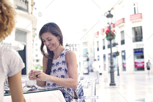 Woman having tea with friends at European outdoor caf_