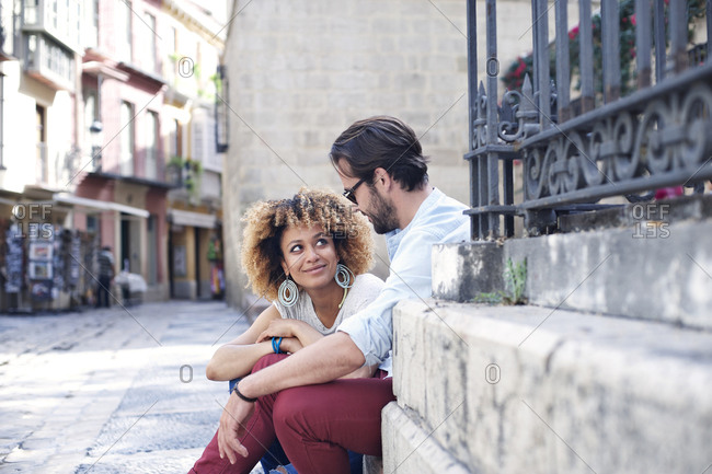 Woman and man sitting on steps in a picturesque European alley