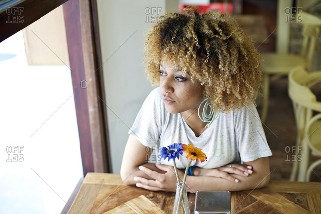Curly haired woman sitting in a caf_ and gazing out the window