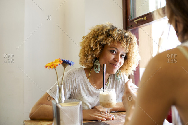 Woman listens to her friend as they sit in caf_
