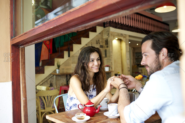 Couple holding hands over a caf_ table