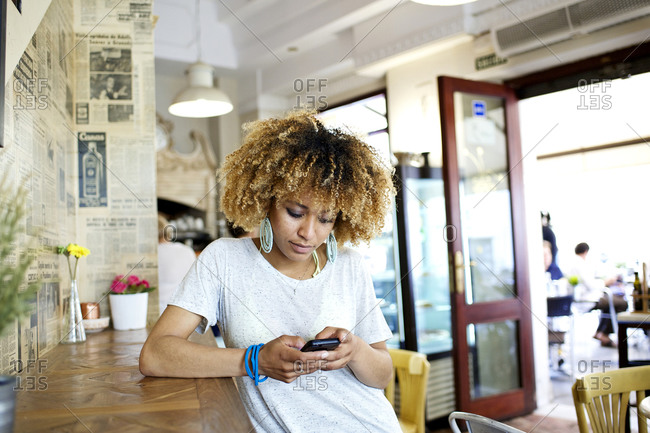 Woman using her smartphone while leaning against a counter in caf_