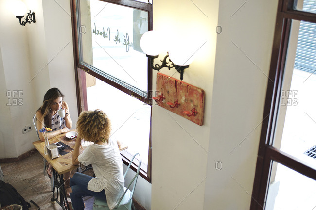 High angle view of two women sitting in caf_
