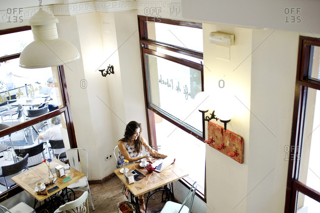 High angle view of woman using laptop at a caf_ table next to window