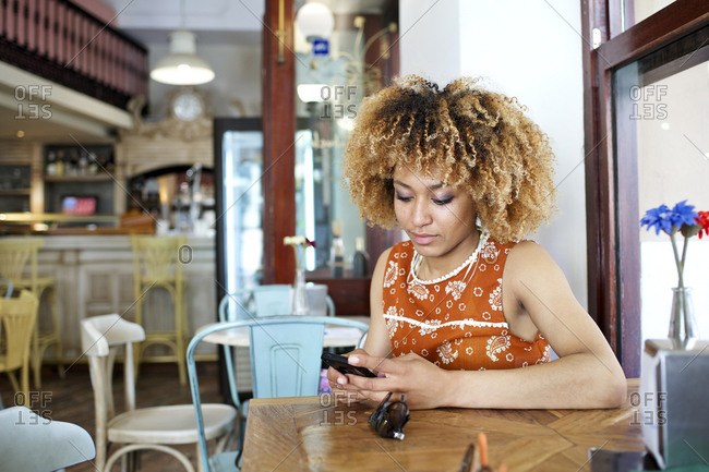 Curly haired woman uses her smartphone at a caf_