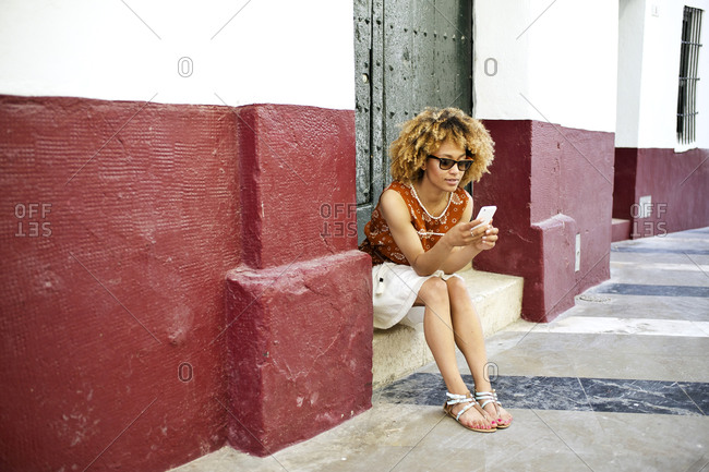 Woman sitting on step using smartphone