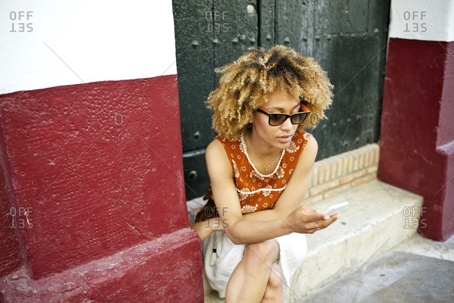 Woman using smartphone on step of building