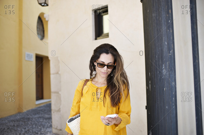 Stylish woman using smartphone in quaint alley