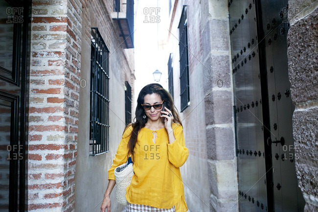 Fashionable woman walks down narrow alley while using cellphone