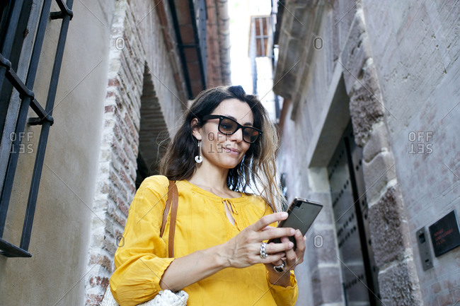 Low angle view of woman using smartphone in alley