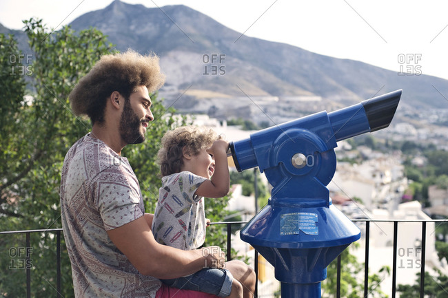 Man holds his son up to look through telescope at scenic overlook