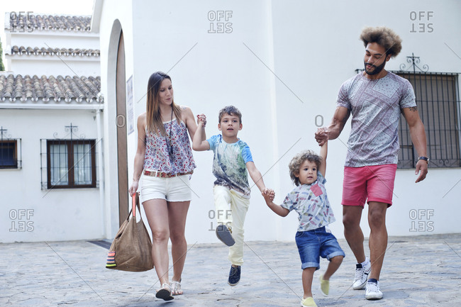 Playful family of four walking past a white stucco church