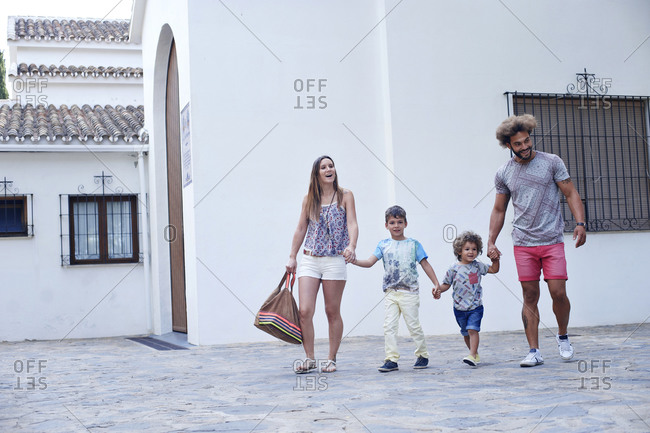 Family of four walk holding hands past a white stucco church