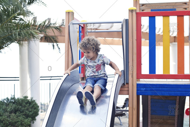 Little boy at top of slide on playground