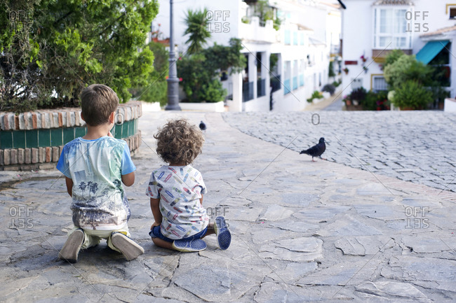 Boys sitting on ground watching pigeons