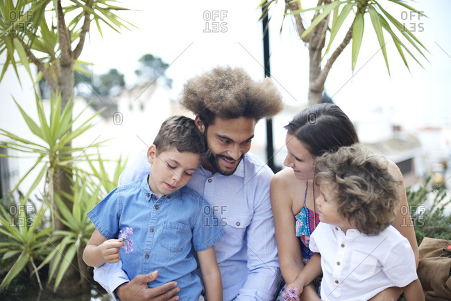 Portrait of family of four with tropical foliage