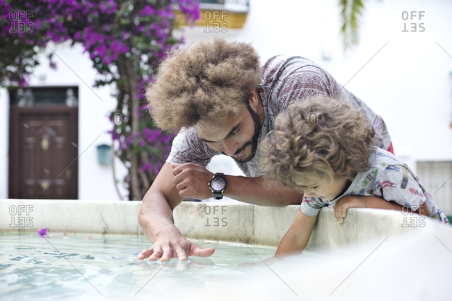 Man plays with son in a fountain