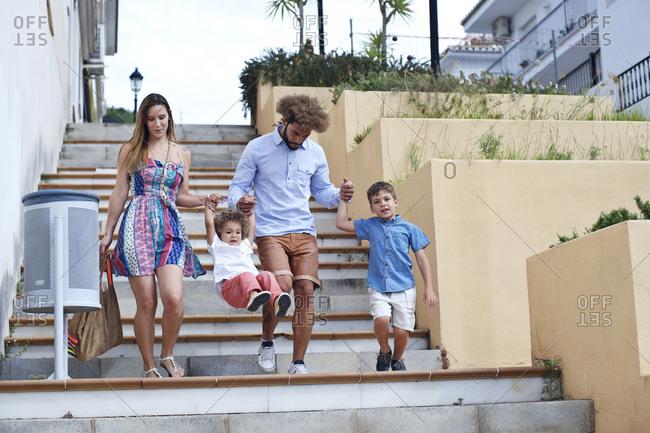 Family of four walking down steps in a coastal southern European hillside town