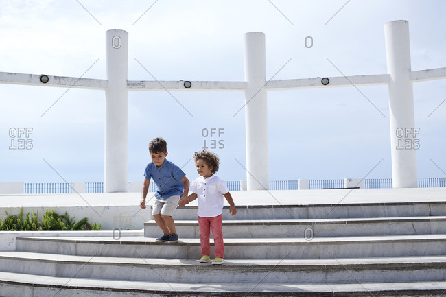 Brothers playing on steps at a scenic overlook